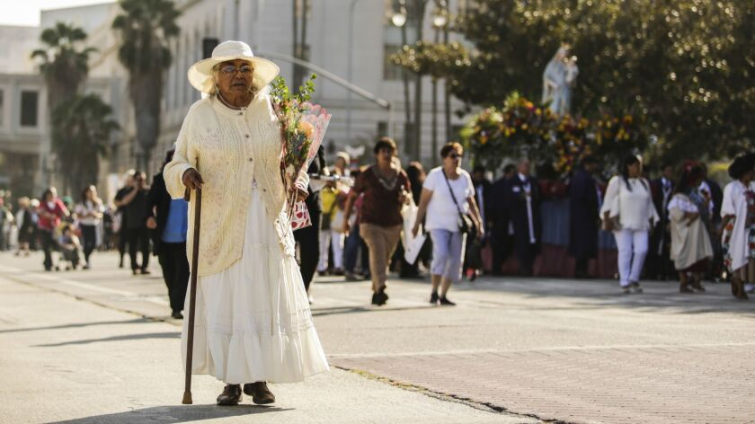 LOS ANGELES, CA -- SATURDAY, AUGUST 25, 2018-- Catarina Atilano prays with her rosary as she walks t