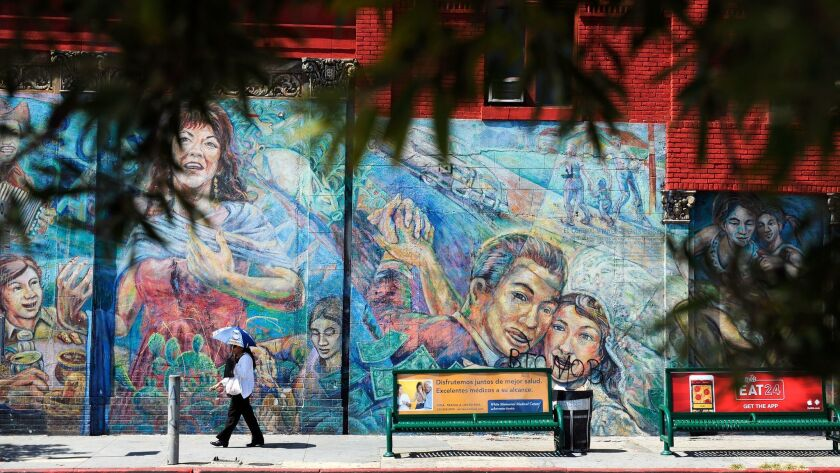 A pedestrian walks past a mural in Boyle Heights in 2015.