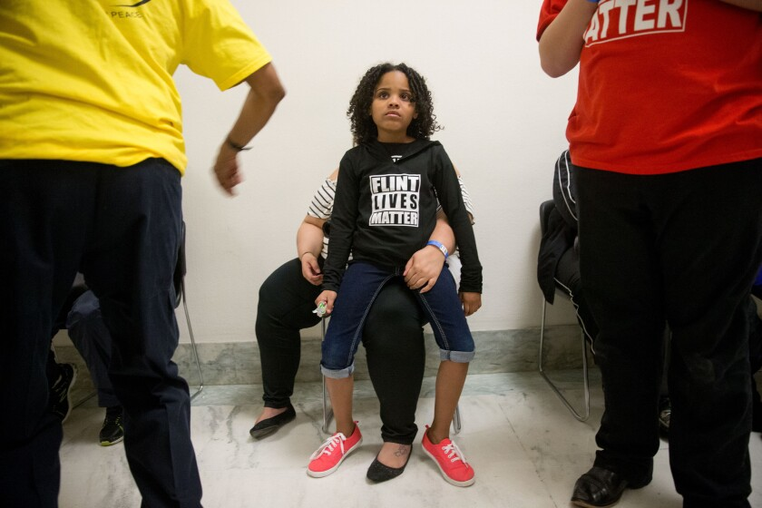 Mari Copeny, 8, of Flint, Mich. sits on the lap of her mother, Lulu Brezzell as they wait outside the room where Michigan Gov. Rick Snyder and EPA Administrator Gina McCarthy testify before a House Oversight and Government Reform Committee hearing in Washington.