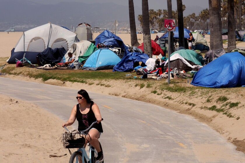 Tents belonging to homeless people abut a beach bike path in Venice.