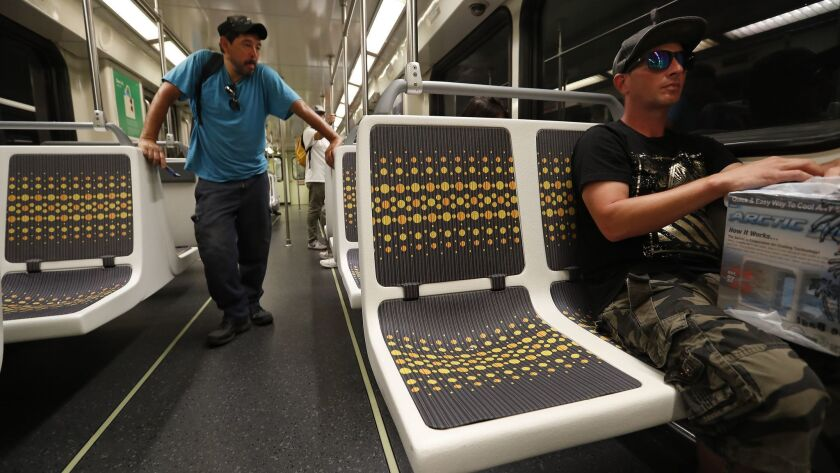 Matt Harrison of Los Angeles tries a new vinyl seat on the Metro Red Line in the San Fernando Valley. The plastic-based fabrics will be installed on all subway cars, Metro says, because they are non-absorbent, cheaper to install and easier to keep clean.