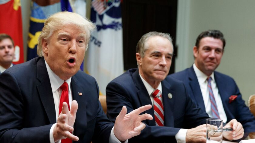 President Donald Trump speaks during a meeting with House Republicans in the Roosevelt Room of the White House in Washington in February, 2017. Seated next to Trump are Rep. Chris Collins, R-N.Y., and Rep. Duncan Hunter, R-Alpine, both of whom have since pleaded guilty to federal offenses.