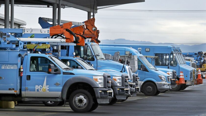 Light-blue PG&E vehicles lined up in a parking lot