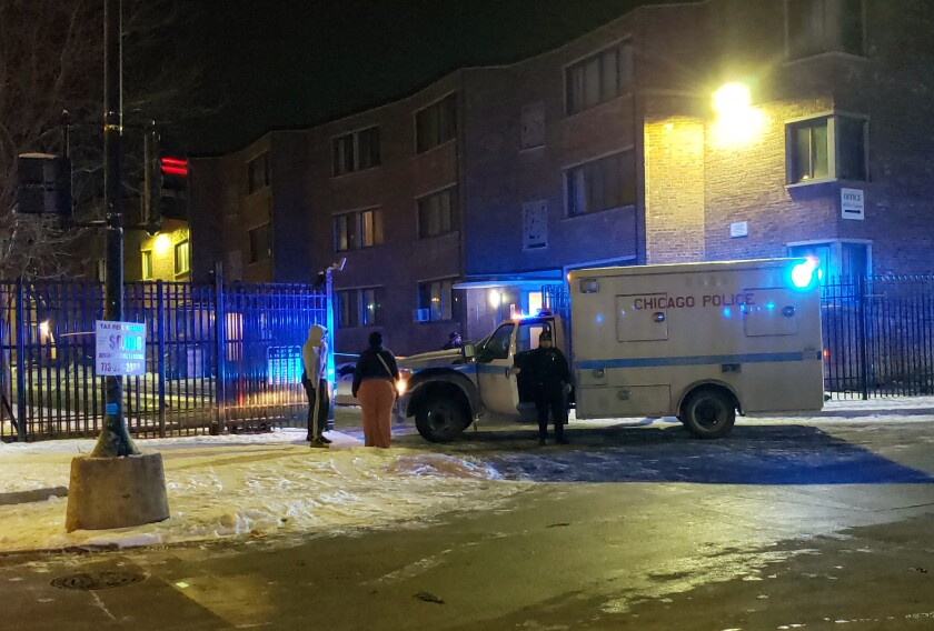 """Emergency responders work the scene of a shooting late Friday, Feb. 14, 2020 in Chicago. Six people, including three minors, were wounded in a shooting at an apartment complex on Chicago's South Side, police said. The Friday night shooting started during a """"gathering"""" inside an apartment unit and spilled into the hall, police said in a release early Saturday. (Nader Issa/Chicago Sun-Times via AP)"""
