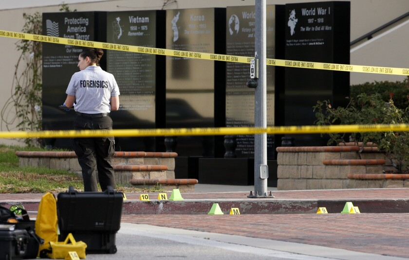 A Glendale Police investigator processes the evidence around a crime scene where one man was found dead in front of the Glendale courthouse and another man suffered serious stab wounds early Monday morning.
