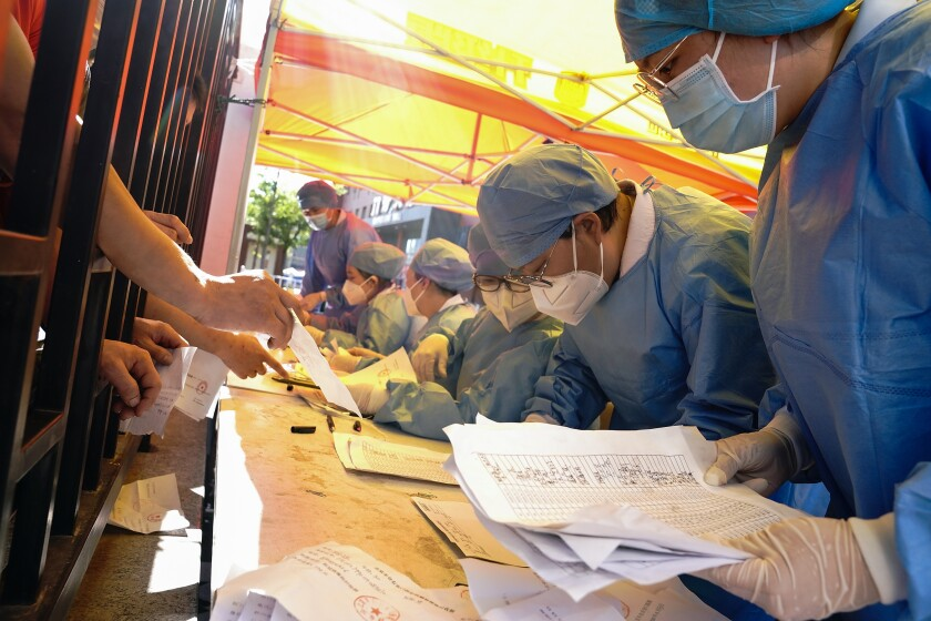 Workers check the names of people waiting to get a COVID-19 test in Beijing.