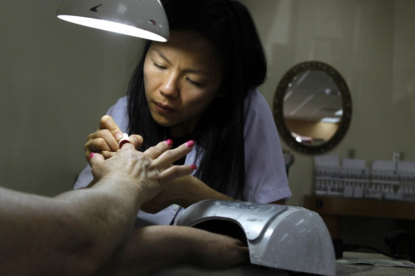 Thuy Vo polishes nails at Queen Nails in Brea in 2012.