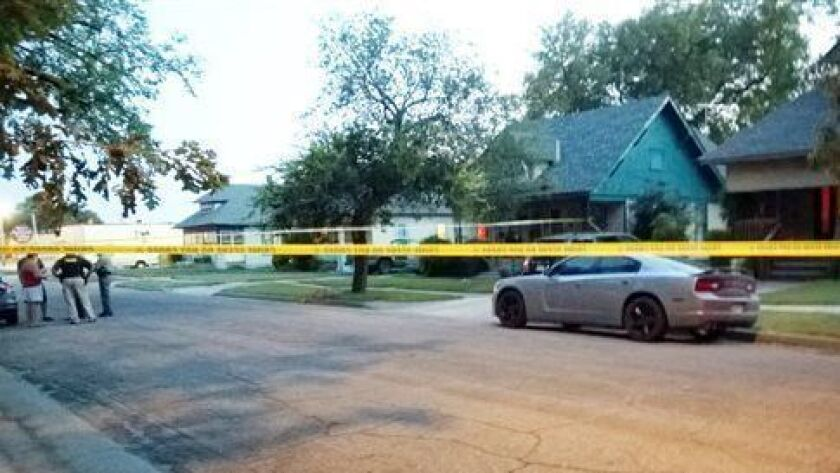 In this July 24, 2014 file photo, police tape surrounds a gray car outside a Wichita, Kan. home, where a 10-month-old girl died after being left inside a hot car.