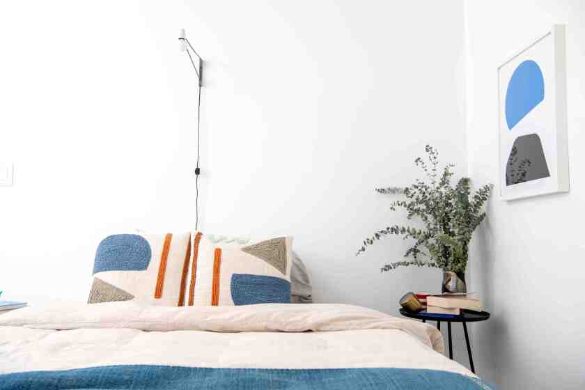 The bedroom features lighting by Brendan Ravenhill and silkscreen prints by Gabriel Stromberg.