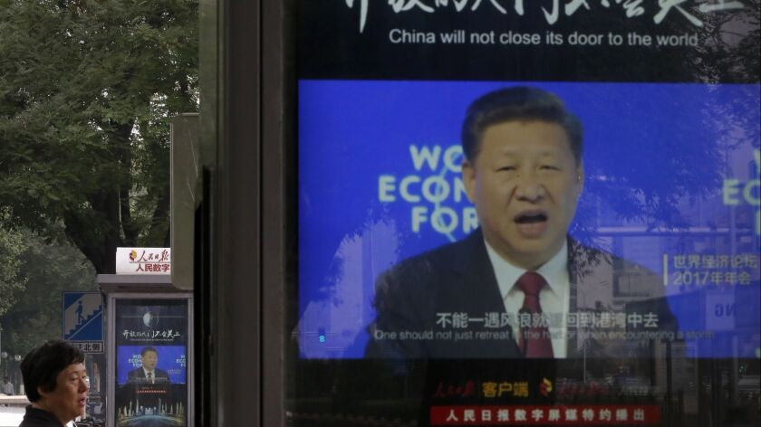 A man walks past electronic display panels in Beijing showing video footage of Chinese President Xi Jinping addressing the World Economy Forum.