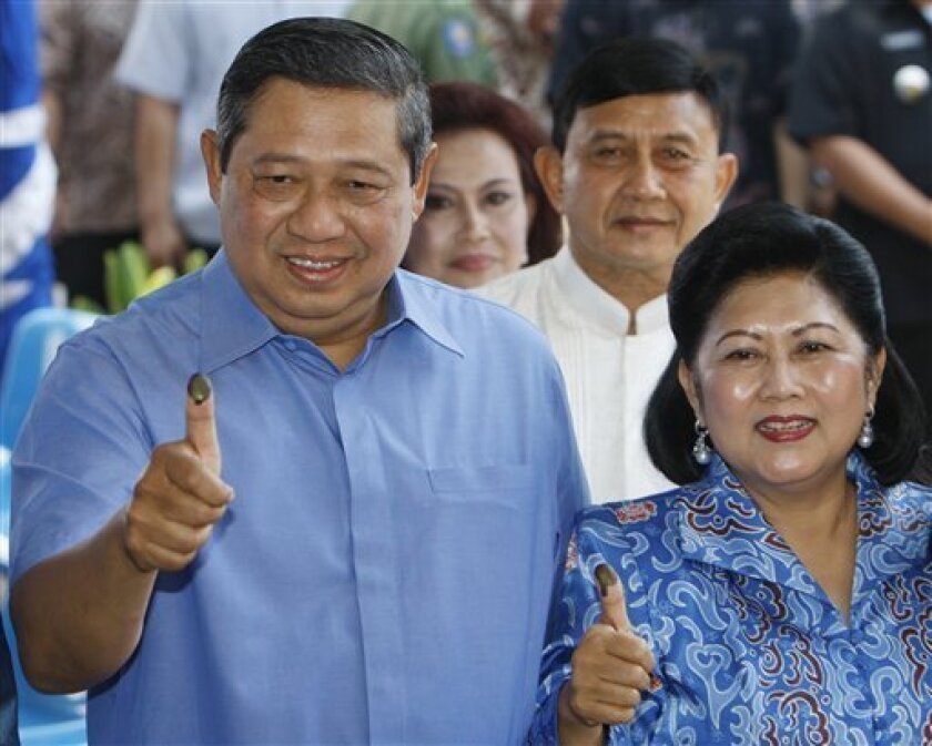 Indonesian presidential candidate and current President Susilo Bambang Yudhoyono , left, shows his ink-stained finger after casting his ballot with his wife, Kristiani Herawati, right, at a polling station Wednesday, July 8, 2009, in Cibubur, on the outskirt of Jakarta, Indonesia. Indonesia's president was poised to win his second term in office on the back of recent economic and political stability, according to early returns Wednesday in the country's presidential election. (AP Photo/Achmad Ibrahim)