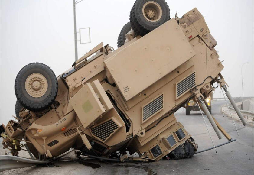 A Mine-Resistant Ambush-Protected (MRAP) vehicle rests on its turret and hood after a 2009 rollover in Iraq.