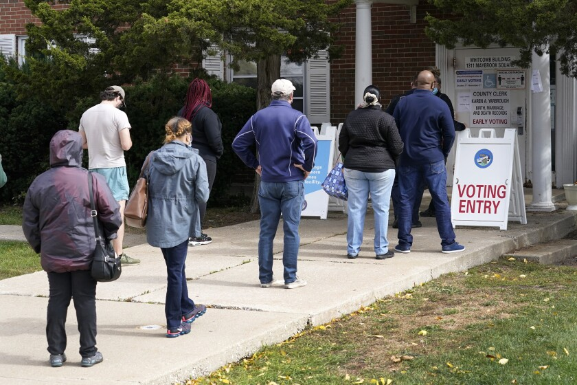 Cook County, Ill., residents wait in line for early voting and other county services Tuesday, Oct. 13, 2020, at a county courthouse in Maywood, Ill. (AP Photo/Charles Rex Arbogast)