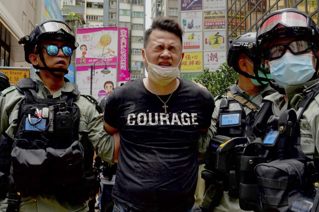 Police detain a protester after being sprayed with pepper spray during a protest in Causeway Bay
