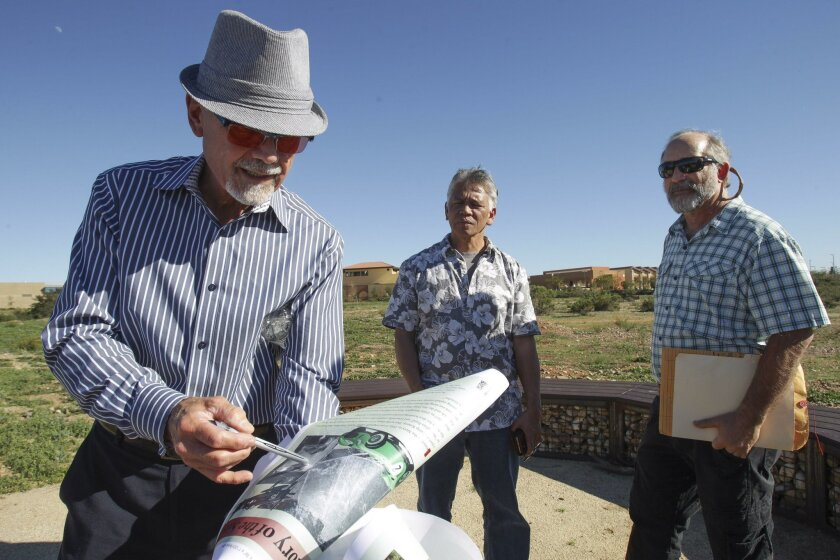 Landscape architect Brad Hilliker points to a picture showing the site's history as an airfield and a racetrack while Miramar College faculty members Fred Garces (center) and Dan Trubovitz stand nearby at the vernal pools trail on campus.