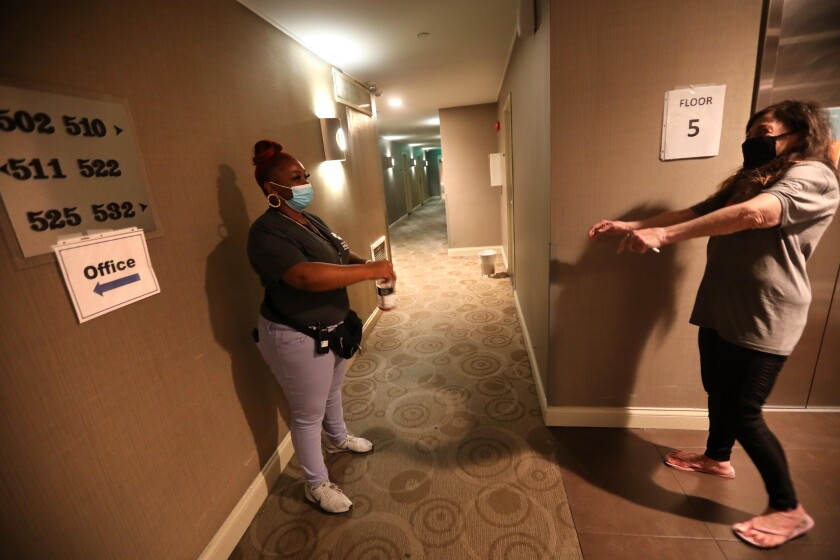 Hotel guest services associate Mia Rogers, left, and guest Fire Wilson keep a social distance while chatting.