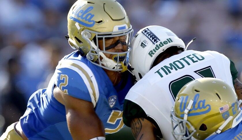 UCLA linebacker Josh Woods, left, helps tackle Hawaii wide receiver Kalakaua Timoteo during a game in September 2017. Woods returned to the practice field Monday.