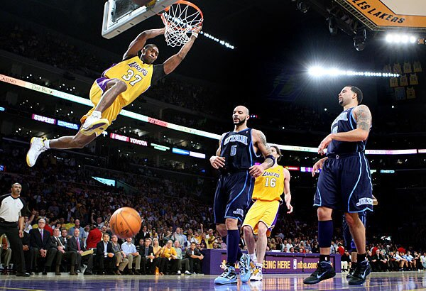 Lakers forward Ron Artest dunks over Utah forward Carlos Boozer, left, and guard Deron Williams in Game 2 of the Western Conference semifinals on Tuesday.