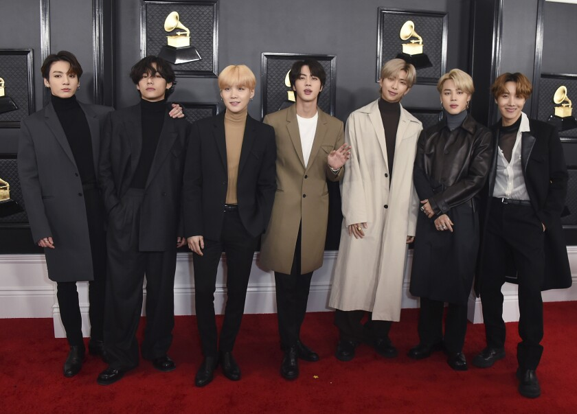 Seven members of BTS pose in a line at the Grammys.