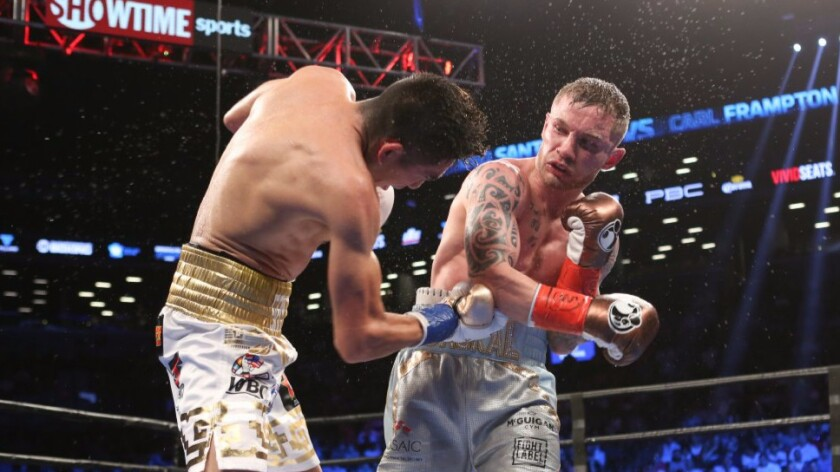 Leo Santa Cruz and Carl Frampton, right, exchange punches during their featherweight title bout in New York on July 30.