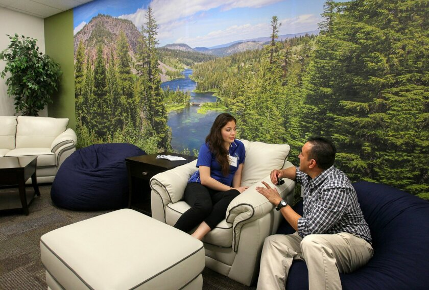 A large mural photo of Mammoth Lakes is displayed on a wall of the lounge area of the new Jan and Esther Stearns Center for ACE Scholars at Cal State San Marcos. At left is ACE Scholar student Jennifer Fiallos and at right is Dominic Barragan, a scholar program specialist at SDSU.