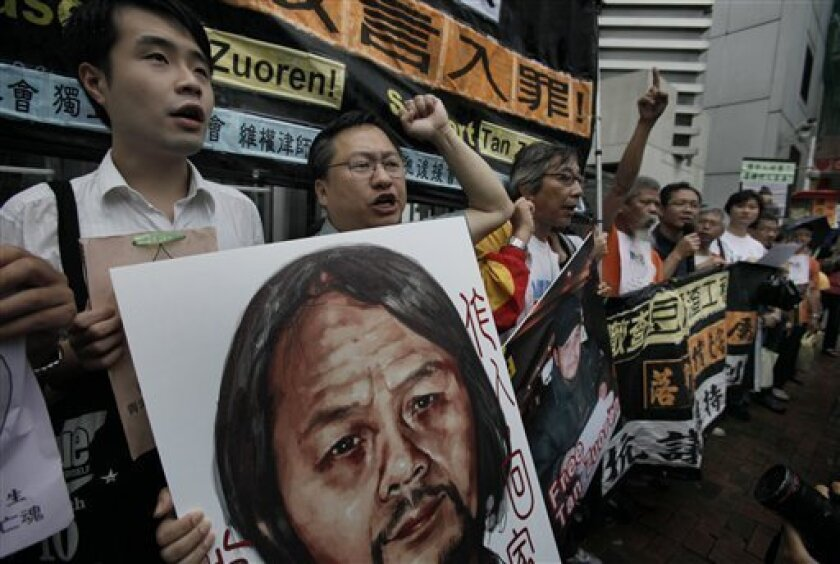 """Protesters raise a picture of Chinese dissident Tan Zuoren during a protest outside the Chinese government's liaison office in Hong Kong Wednesday, June 9, 2010. A Chinese court Wednesday upheld Tan's five-year sentence for subversion passed down after he investigated the deaths of children crushed in their schools during the 2008 Sichuan earthquake. About 30 human rights activists protested the court's decision Wednesday. The Chinese words read """" Return the freedom to Tan Zuoren. """" (AP Photo/Vincent Yu)"""