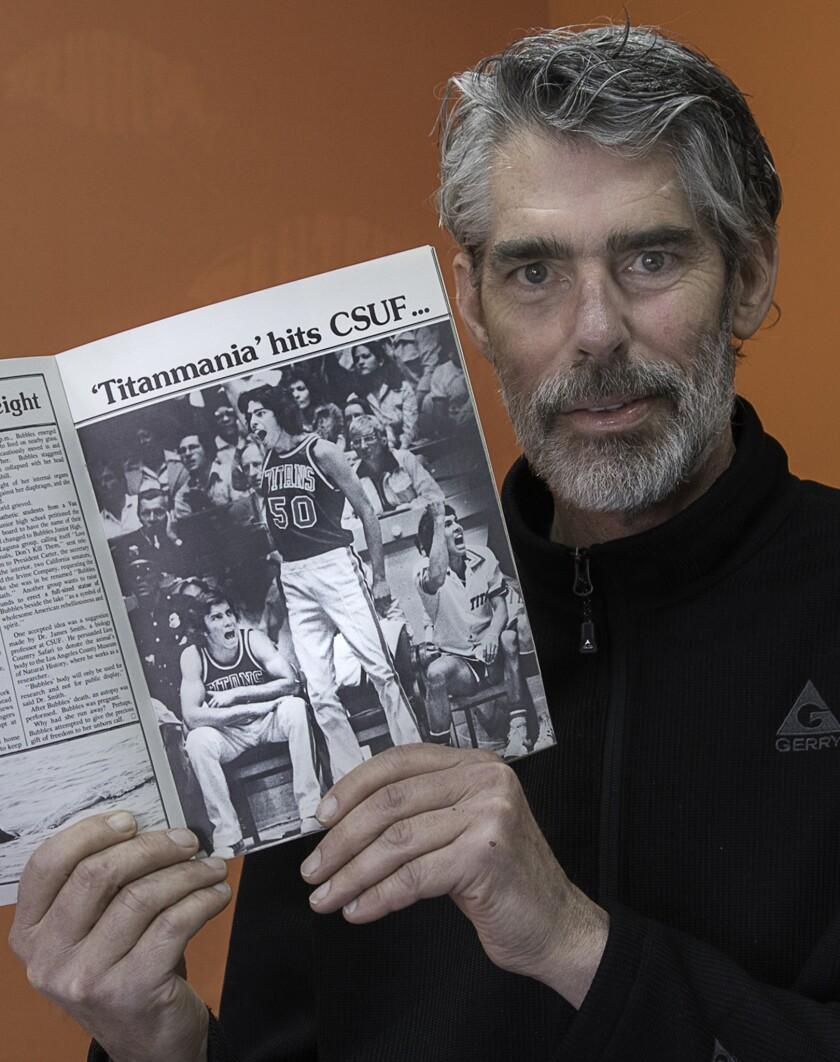Former Cal State Fullerton basketball star Tom Corvin holds up a program of himself (50) celebrati
