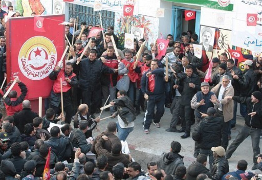 Members of the leftist UGTT union, background, react during clashes with League members during a rally to commemorate the 1955 assassination of a historic member when they were attacked by the League for Protection of the Revolution, Tuesday, Dec.4, 2012 in Tunis. League members are considered to be close to the Ennahda Party, which dominates Tunisia's post-revolution coalition government (AP Photo/Amine Landoulsi)