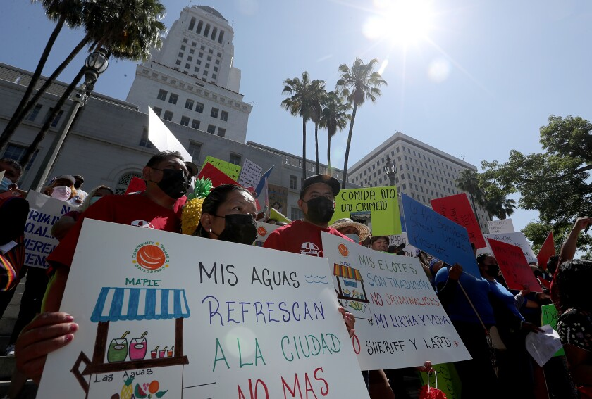 A crowd of people carry signs, some of them written in Spanish.
