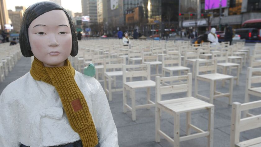 """Statues symbolizing """"comfort women"""" stand at Gwanghwamun Square in front of the Japanese Embassy in Seoul as part of a performance called """"A Promise Inscribed on an Empty Chair"""" on Wednesday."""