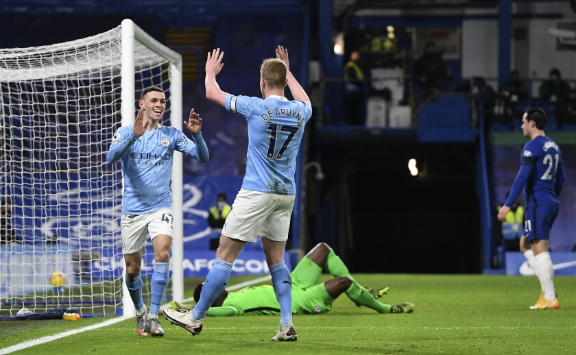 Manchester City's Phil Foden celebrates with Manchester City's Kevin De Bruyne after scoring his side's second goal during the English Premier League soccer match between Chelsea and Manchester City at Stamford Bridge, London, England, Sunday, Jan. 3, 2021. (AP Photo/Ian Walton/Pool)