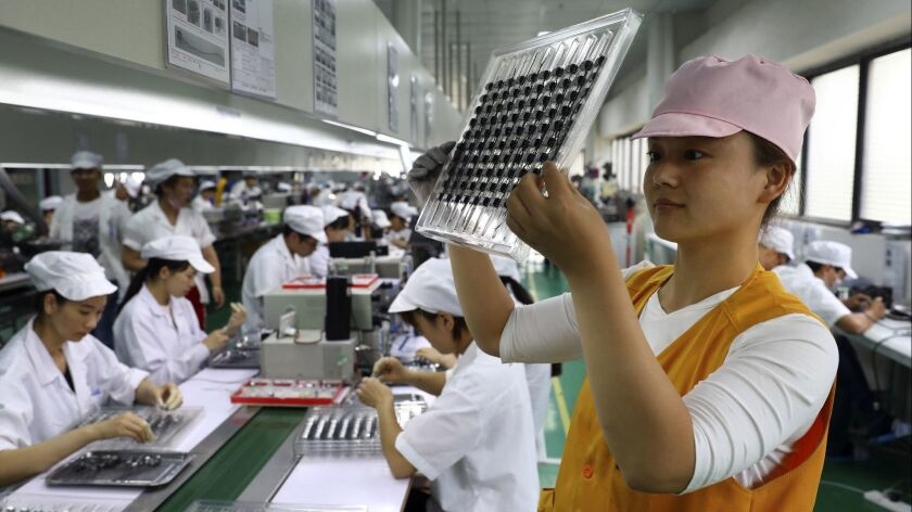 In this June 23, 2018, photo, a worker inspects the micro-motors for handsets at a factory in Huaibe
