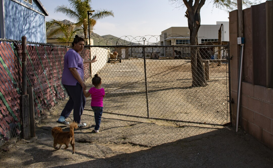 Jovita Diaz and 3-year-old Arianna head to the backyard, which has a view of a warehouse