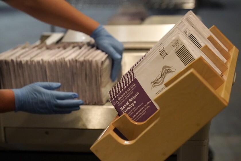 Hands organize ballot return envelopes