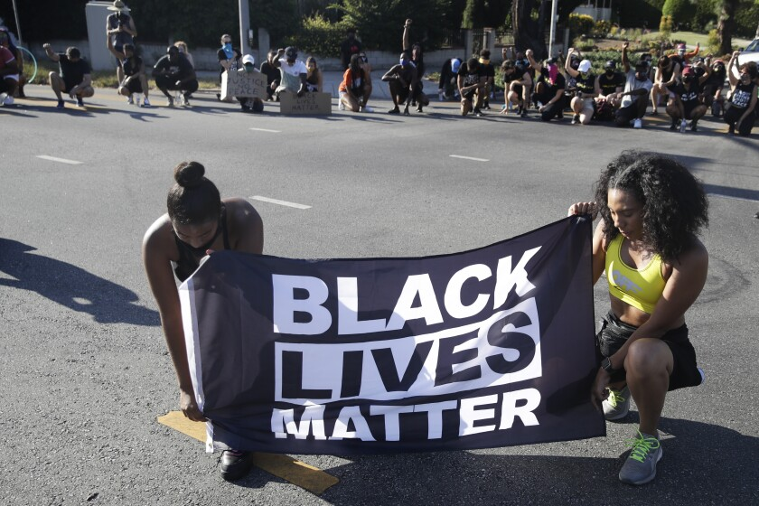 Two women kneel while holding a Black Lives Matter banner during a demonstration.