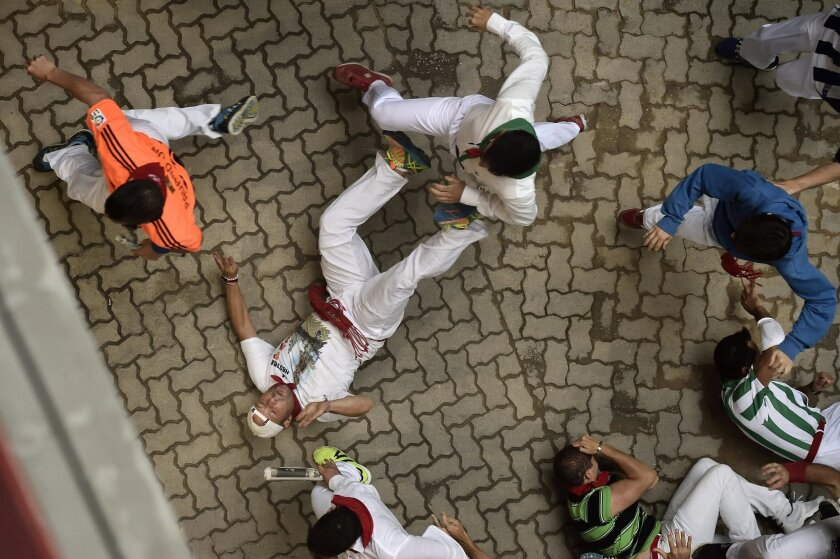 A reveler falls entering the bullring during the sixth running of the bulls with Victoriano del Rio Cortes's fighting bulls, at the San Fermin Festival, in Pamplona, northern Spain, Tuesday, July 12, 2016. Revelers from around the world flock to Pamplona every year to take part in the eight days of