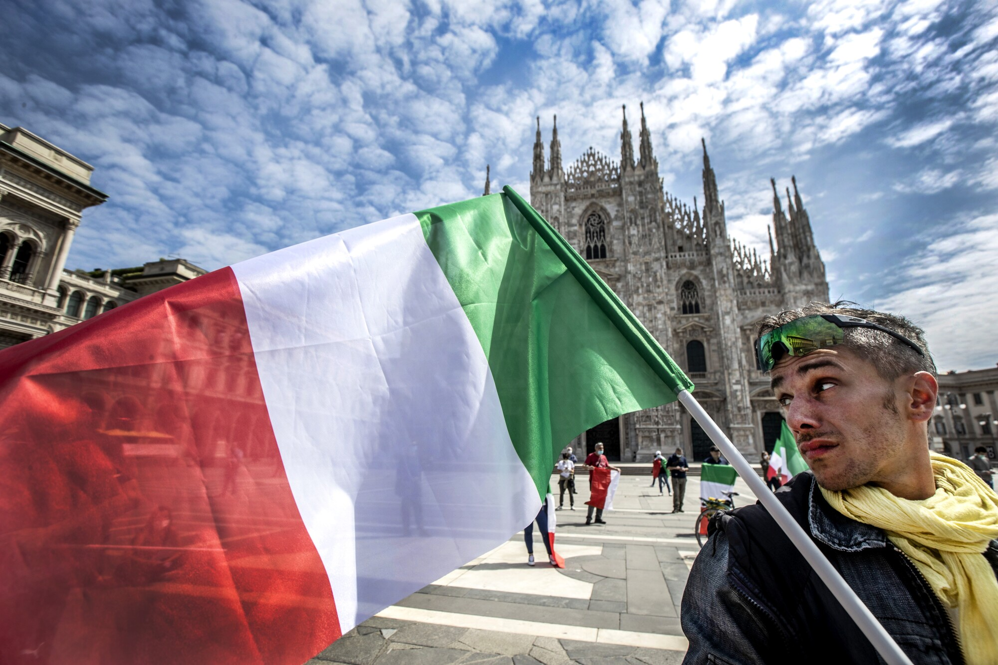 A man holds an Italian flag in front of the Duomo cathedral in Milan on Monday. Italy has begun allowing citizens to return to work and easing restrictions imposed to stem COVID-19 infections.