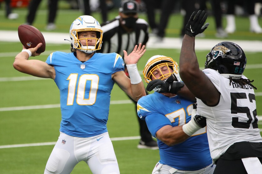 Quarterback Justin Herbert of the Los Angeles Chargers throws a pass against DaVon Hamilton of the Jacksonville Jaguars.