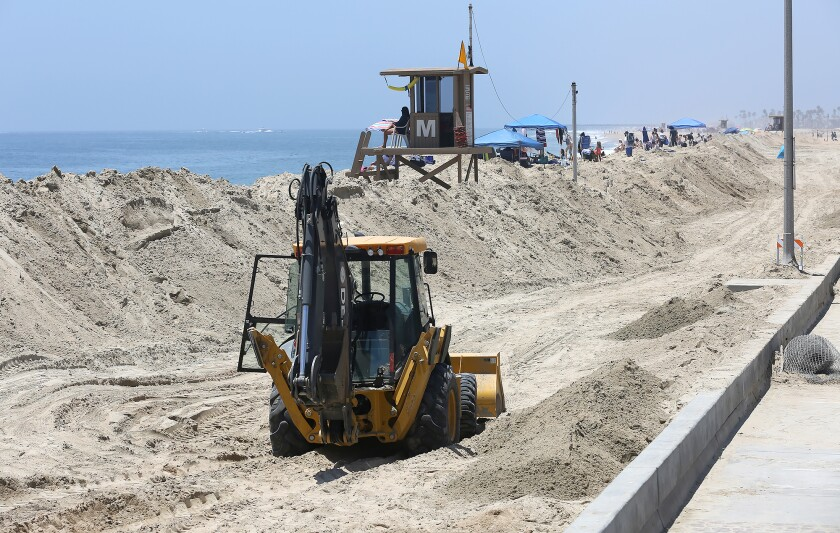 A sand berm was rebuilt to hold off big waves and high tides at Balboa Pier in Newport Beach.