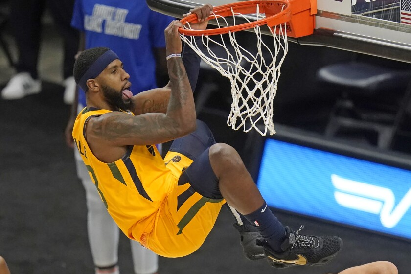Utah Jazz forward Royce O'Neale hangs from the rim after dunking against the Detroit Pistons during the second half of an NBA basketball game Tuesday, Feb. 2, 2021, in Salt Lake City. (AP Photo/Rick Bowmer)