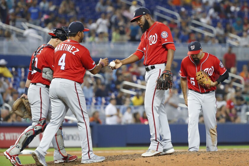 Washington Nationals manager Dave Martinez (4) takes the ball from relief pitcher Wander Suero during the seventh inning of a baseball game against the Miami Marlins, Sunday, Sept. 22, 2019, in Miami. Sure and Hunter Strickland allowed two runs apiece in the seventh, and Tanner Rainey gave up an RBI triple by Starlin Castro as the Marlins rallied from a 3-1 deficit to defeat the Nationals 5-3. (AP Photo/Wilfredo Lee)