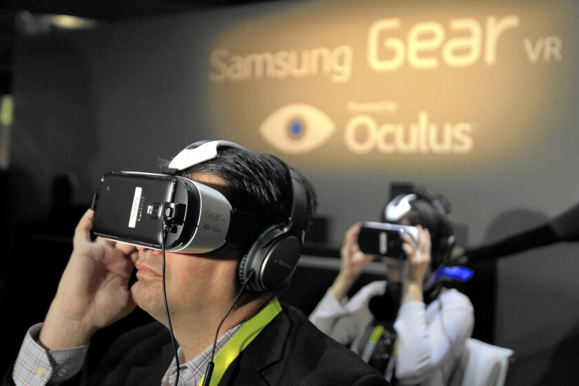 Chris Hall, left, tries out a virtual reality headset during the 2015 International CES in Las Vegas this week.