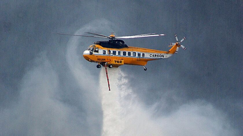 """A S-61 Sikorsky """"Sea King"""" helicopter drops water on a section of the the Ricco Fire near Piedmont,"""