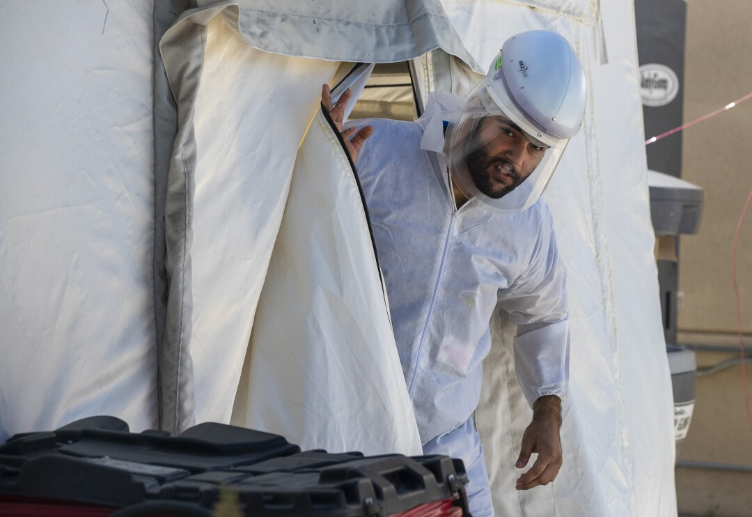 A scrub tech wearing a face shield and PPE leaves the OB triage tent at Providence Holy Cross Medical Center