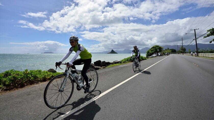 Cyclists pedal past Mokolii Island off Oahu's eastern shore during the annual Honolulu Century Ride.