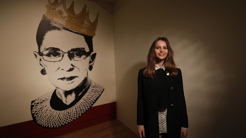 "Felicity Jones poses near an image of Justice Ruth Bader Ginsburg at the exhibit ""Notorious RBG: The Life and Times of Ruth Bader Ginsburg"" at the Skirball Cultural Center."
