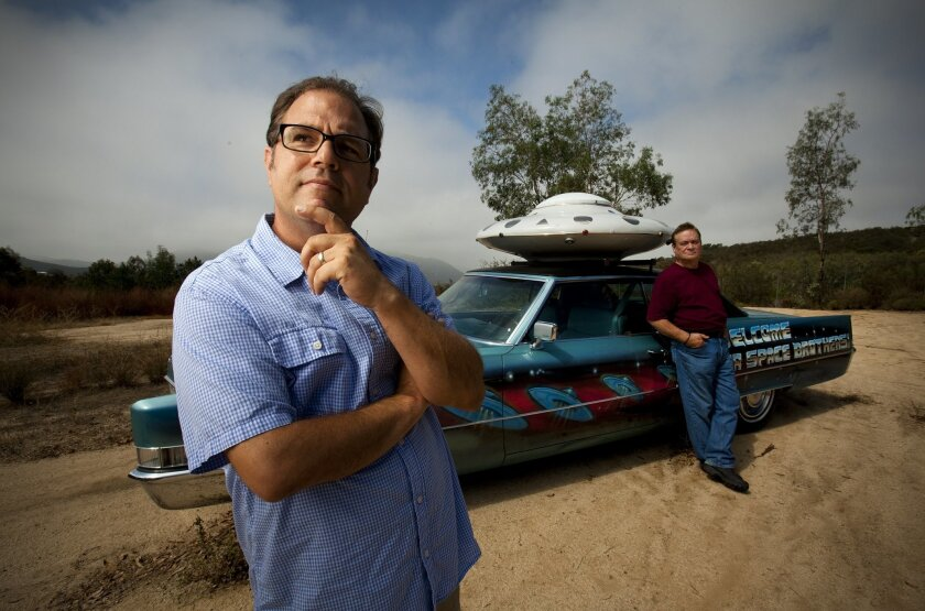 David Moye, left, who covers weird news for the Huffington Post, at the spot in Jamul where William Proctor, right, and others with the Unarius Academy of Science believe spaceships will land. The academy's trick-out Cadillac is an East County icon.
