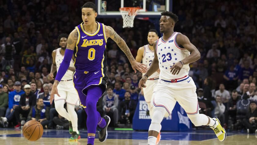 Los Angeles Lakers' Kyle Kuzma, left, drives upcourt agaisnt Philadelphia 76ers' Jimmy Butler, right