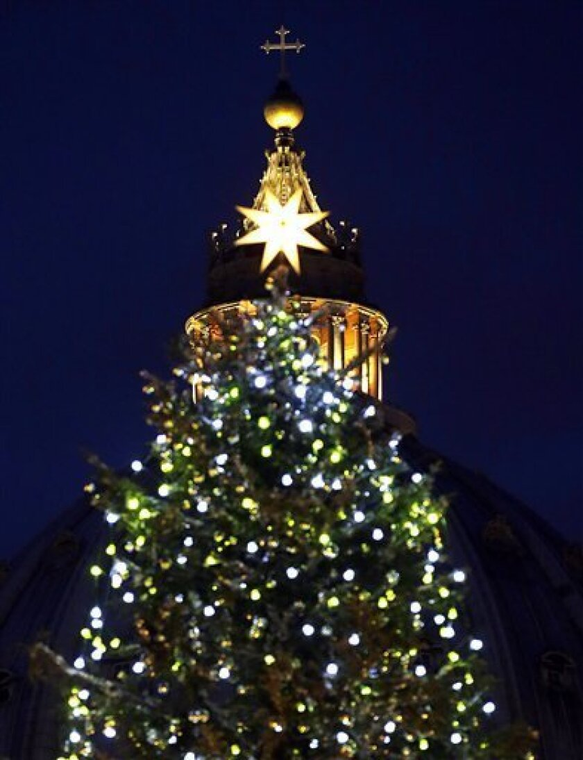 """The 24 meters (78.74 feet) Christmas tree is lit in St. Peter's square at the Vatican, Friday, Dec. 14, 2012. The Christmas season kicks off Friday at the Vatican with the traditional lighting of the tree in St. Peter's Square — and a reminder from the Pope about what happened when the """"lights"""" of God were turned off in past atheistic regimes. (AP Photo/Gregorio Borgia)"""