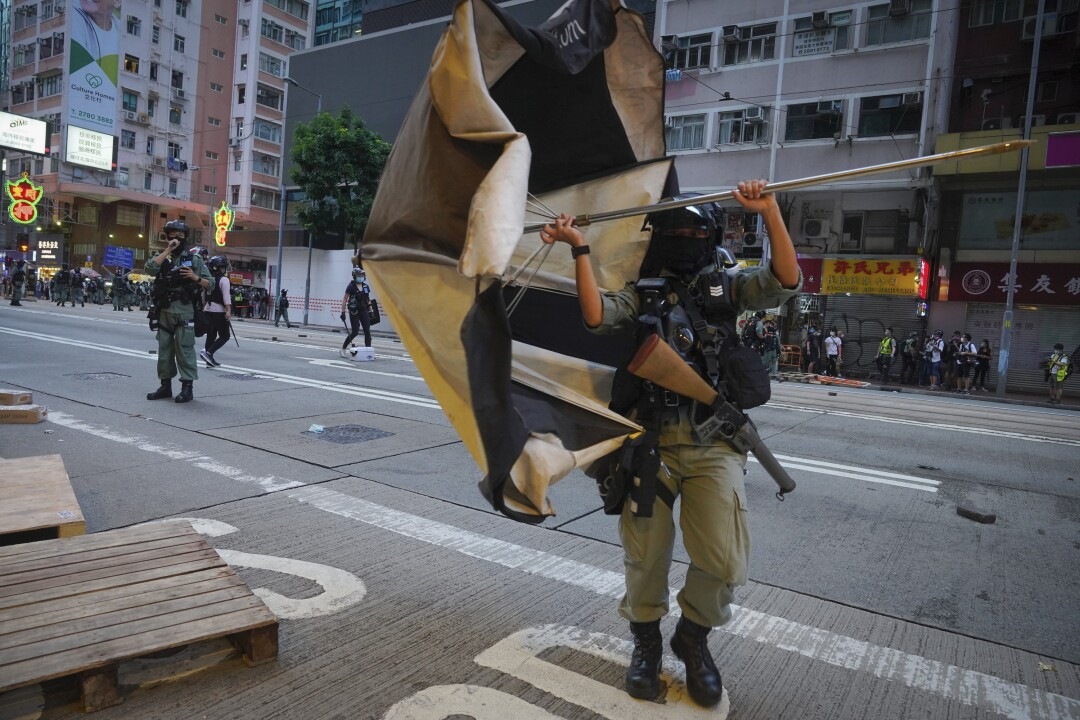Police remove a giant umbrella roadblock from a main road in Hong Kong on Wednesday.
